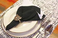 Os mais modernos podem colocar o guardanapo em cima do prato e, nesse caso, dá para soltar a imaginação para criar combinações de cores e de porta-guardanapos. Aqui, a louça utilizada foi a clássica Flamingo Sofia com filete em ouro.
