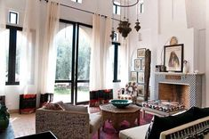 Morrocan living space - I like how the wall shapes mimic minarets, subtle.  The mantle is gorgeous. Lots of geometric shapes, but some femininity with the flowing, tall curtains.