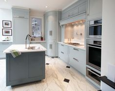Gray kitchen design with curved doors for corner cabinet