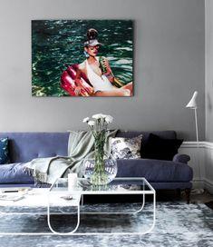 Gråmålad vägg och blå soffa. Glasbord.