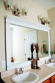 Make Photo Gallery Framing mirror using crown molding and spray paint so much cheaper than buying the huge mirror already attached to a huge frame