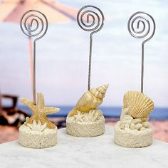 It's as if they were scooped right off the ocean floor - these beach wedding favors really capture that beachy feel.With a carefully crafted resin base that resembles sand, coral and shells, each of these beach themed wedding favors has one of three assorted sea treasures, realistically recreated, as its dramatic centerpiece. Each has a wire coil rising above the shell base that acts as the place card holder - also perfect for holding a note or photo in your guest's home or office. Size: 4…