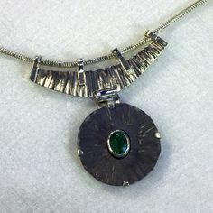 Charles Pinckney - Jewelry Artist Titanium Sterling Gold | Pendant Pendant fabricated of forged titanium, forged sterling and emerald set in a sterling bezel. Dimensions: 1.9 x 2.0 x 0.25 inch.