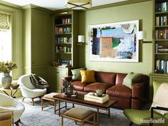 """The library, with Farrow & Ball's Olive paint and Phillip Jeffries's Vinyl Thai Silk wall-covering, represents """"a warmer zone.""""  Tommi Parzinger coffee table with pullout stools and Kurt Østervig chairs for Rolschau MØbler date from the 1950s. Sofa by A. Rudin. Rug by Stark.   - HouseBeautiful.com"""