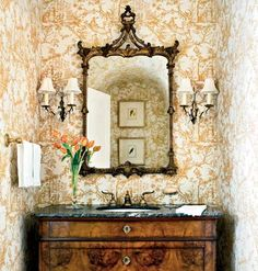 Very elegant powder room. I love the Chinoisere mirror & the beautiful wood vanity.The black marble top gives that touch of black some people think all rooms need. The wallpaper is the perfect backdrop.