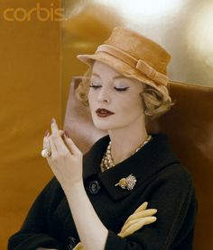 Model wearing hat of feathers, worked to look like silk, in a pale orange, by Adolfo of Emme. Worn with brown wool tweed coat, pinned with Verdura brooch, 1959