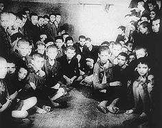 A group of hungry Jewish children pass the time of day in a crowded room in the Warsaw Ghetto.