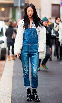 Mulher posa para foto na rua usando camisa jeans clara, jardineira jeans azul, botas de verniz preta, casaco faux fur bege