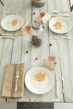 Simple rustic Fall table setting with leaves, pinecones, cranberries, and…