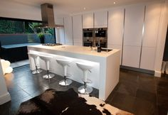 This contemporary high gloss island kitchen design is finished in a Polar white high gloss satin lacquer. The Polar white is sharper than other whites and in this design lighting integrated within the breakfast bar effectively shows off its crisp and slee White Kitchen Design, Open Plan Kitchen, Handleless Kitchen, Modern Kitchen, London Kitchen, Kitchen Layout, Contemporary Kitchen, White Kitchen Island, Kitchen Installation