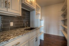 Walk-in pantry with counter, sink, cabinets and built-in shelving.