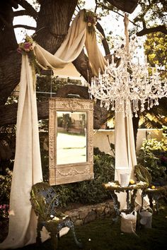 Everything about this picture says you! —from the candelabra to the mirror frame to the draping, to the roses, to the old iron furniture... Feels Southern AND Vintage.