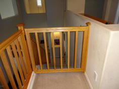 A nice looking custom baby gate for the top and bottom of the stairs. DIY baby gate for stairs with railings.