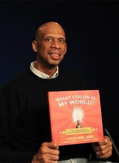 """Former NBA player Kareem Abdul-Jabbar holds a copy of his new children's book, """"What Color is My World?: The Lost History of African-American Inventors,"""" in New York."""