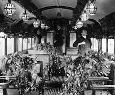 The interior of a tube train decorated with foliage for the Christmas Season, ca. 1922.