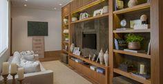 A estante de madeira é o grande destaque desta sala de TV. Em cada espaço há detalhes que remetem às lembranças da família.