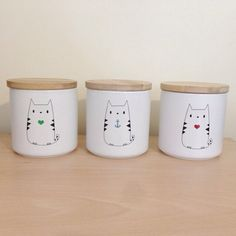 White ceramic jar with wooden lid and cute cat anchor design