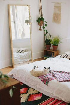 Floor mirror and plants, bed on floor