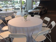 White Hercules chairs and round tables at the Jim Ellis Audi Atlanta showroom. The Audi doesn't hurt the decor of the room either. Table Linen Rentals, Table Linens, Corporate Event Planner, Chairs For Rent, Farmhouse Table, Round Tables, Atlanta, Hercules, Dining Table