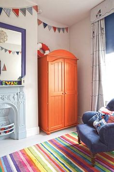 A large terra cotta painted armoire serves as a cheerful accent, without overwhelming the whole room. See more Pantone Celosia Orange Furniture, Room, Redo Furniture, Home, Painted Furniture Cabinets, Blue Gray Bedroom, Grey Walls, Orange Painted Furniture, Painted Armoire