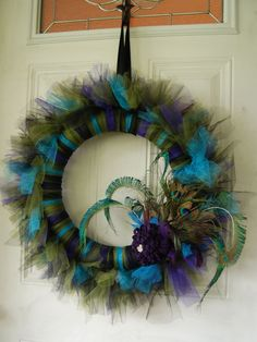peacock wreath. awesome. Great addition to the peacock dorm room decor. Styrofoam, tulle and feathers...light weight, easy to hang with and strip hooks.