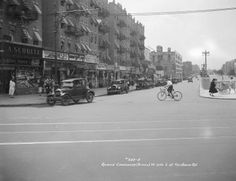 """""""Grand Concourse west side, south at Fordham Road, Bronx. Corner of East Fordham Road and Grand Concourse, parked cars and store fronts at left, man on bicycle crossing street, lady and baby carriage about to cross. 1927.""""(Courtesy of the NYC Municipal Archives)"""