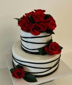 White and black cake with some red roses.