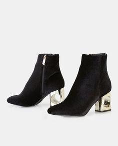 """<p>A pair of must-have booties featuring a velvet upper and a cutout heel design.</p>  <ul> <li>5.5"""" Shaft</li> <li>3"""" Heel</li> <li>Zip Closure</li> <li>Lightly Padded Footbed</li> <li>Textured Sole</li> <li>Man Made Materials / Metal</li> <li>Imported</li> </ul>"""