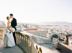 Stunning photo of the bride & groom kissing on the balcony