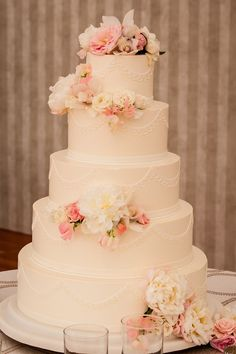 The wedding cake by Mark Soliday at Confectionary Designs in Newport, decorated with peonies and roses.