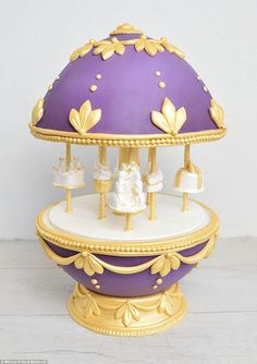 Faberge egg inspired cake.   Yellow Bee Cake Company's amazing violet and gold carousel which features cakes as rides instead of the usual animals