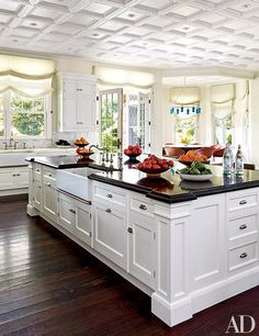 The kitchen, painted in a Farrow & Ball White features Roman shades in an Old World Weavers fabric | archdigest.com