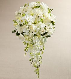 The FTD® White Wonders™ Bouquet is an exquisite display of wedding elegance. An incredible array of white blooms, including Dendrobium Orchids, roses, Asiatic Lilies, freesia, spray roses, and mini hydrangea are offset by beautiful lush greens and arranged in a cascade fashion to create a memorable bouquet that will complete your bridal look with its sweet sophistication.