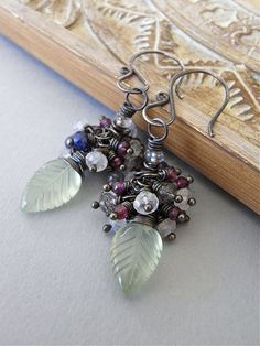 The Gardening by the Moon earrings - carved prehnite leaves are topped with moonstone, sapphire, rhodolite garnet, and black rutile quartz.  All metal is oxidised sterling silver.