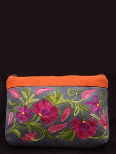 This delightful clutch has a grey suede base and bright red border with a zipper closure.    This little charm is crafted with beautiful intricate embroidery in a floral pattern in bold hues like pinks, purples and greens.