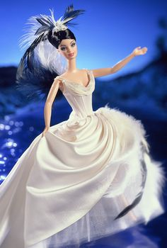 THE SWAN Barbie (2000) ... Birds of Beauty Collection ... Barbie looks so elegant wearing an exquisite off-white, satin, ballerina-style gown. Ivory organza detailing decorates the corset-style bodice, which is accented by a delicately beaded décolletage. Reminiscent of a swans silhouette, the full, draped, satin skirt falls gracefully over an ivory tulle underskirt. Black and white feather flourishes and a beaded, feathered headpiece complete her dramatic ensemble.