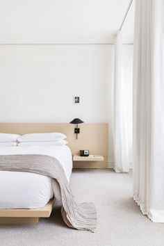 Minimalist bedroom with a wood headboard, simple linens, and floor to ceilings sheer curtains