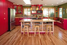 Love this kitchen!!  The red with the green and the yellow/orange pendant lights, the island with the shelves, the bench under the windows.