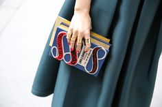Olympia Le-Tan clutch, Balenciaga rings, teal full skirt.