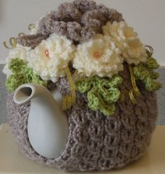 knitted to my own design in a lovely soft caramel chunky wool, this tea cosy is in a mock cable pattern with a ribbed top and fluted, picot top edge....it is soft, warm and thick to keep tea hot....  i crocheted 5 large soft cream roses in a rolled design with frilly edges.....each rose has a lovely peach glass pearl centre.......  i also 5 crocheted sprigs of little leaves in a pure new wool in a lovely shade of green, each with a rose on top.........  the crochet cord which threads through…