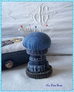Denim pincushion. It looks like the cut-off seams were glued into discs, then stacked up and glued, with the pincushion on the top. Cute!