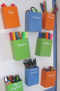 Metal bins covered with vinyl labels, placed on a magnetic board that hangs on the wall t organize art supplies. Board and bins from Ikea
