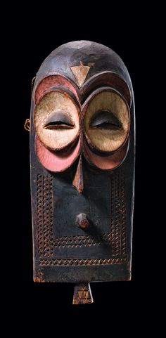 "Africa | 'Eluba or Emangungu' mask from the Bembe people of DR Congo | wood, matt patina, polychrome paint | Used at circumcision rites by the ""butende bwa eluba"" society. The eyes should remind on an owl, which is said to have close connections to the spirits of nature. The masks are attached to a costume of banana leaves and bark. They are worn by initiated boys while begging for food in the village during the seclusion period."