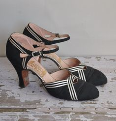 Absolutely amazing rare vintage early 1930s designer sliver stripe heels. The front as a unique small triangle cut out. The straps are accented with a art deco rhinestone buckle. There is also a small cut out around the ankle strap. Original wood soles. These rare shoes are truly stunning, and a glamorous deco touch any ensemble. (Etsy)