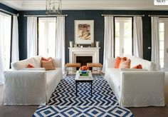 navy walls, chevron rug, orange pillows, fireplace, drapes...it's all good.