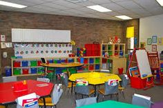 Classroom layout idea - like the cubbies, the kidney table, the pockets on the back of the chairs, the colors, and the literacy center partially visible at the right of the photo (easel and rocking chair). Tables are great for group work and centers.