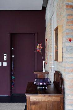 Porta do elevador pintada na cor vinho dá acesso direto ao living. O forro tem rebaixo feito com gesso e o piso foi coberto por laminado melamínico cinza chumbo, da Uniplac, linha Pertech
