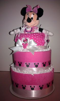 Minnie Mouse Diaper Cake by DeRusDesigns. Filled with great Minnie Mouse Baby themed gifts for the new Mom. Socks, Bib, Bows, Pacifier, Hooded towel, Flanel blanket, bodysuit, bottles, plush toy.