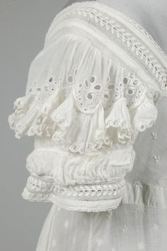 Sprigged muslin day dress  c1825 / embroidered overall with minute leaves and flower heads / DETAIL: puffed cutwork sleeves edged in ruffles of muslin, similar broad ruched band to hem