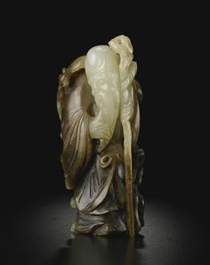A WHITE AND BROWN CARVED JADE FIGURE OF SHOULAO -  QING DYNASTY, 18TH CENTURY. Via Sotheby's